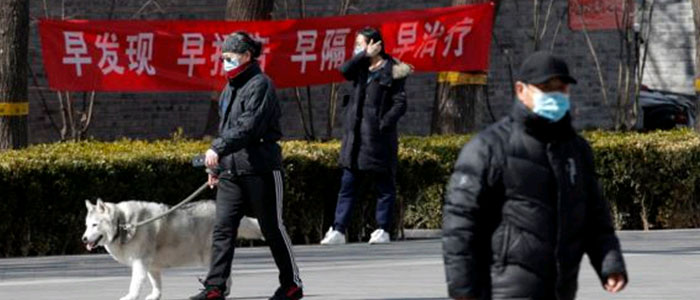 Residents who are wearing protective face masks hang a propaganda banner in which written ''Early detection, early reporting, early isolation and gets early treatmen' fighting the coronavirus outbreak in Beijing